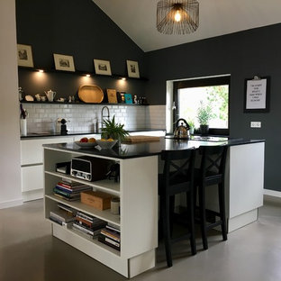 Inspiration for a mid-sized contemporary galley open plan kitchen in Hanover with a drop-in sink, flat-panel cabinets, quartz benchtops, with island, grey floor, white cabinets, white splashback, subway tile splashback, vinyl floors and black benchtop.