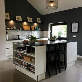 ハノーファーの中くらいのコンテンポラリースタイルのおしゃれなキッチン (ドロップインシンク、フラットパネル扉のキャビネット、クオーツストーンカウンター、グレーの床、白いキャビネット、白いキッチンパネル、サブウェイタイルのキッチンパネル、クッションフロア、黒いキッチンカウンター) の写真