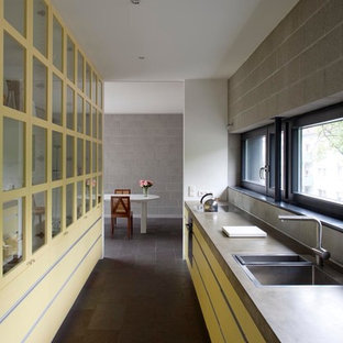 Mid-sized contemporary enclosed kitchen designs - Inspiration for a mid-sized contemporary single-wall slate floor enclosed kitchen remodel in Berlin with a drop-in sink, flat-panel cabinets, yellow cabinets, concrete countertops, black appliances and no island