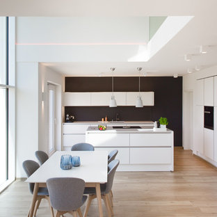 Inspiration for a large scandinavian open plan kitchen in Hamburg with an undermount sink, flat-panel cabinets, white cabinets, quartzite benchtops, black splashback, glass sheet splashback, black appliances, vinyl floors, with island and beige floor.