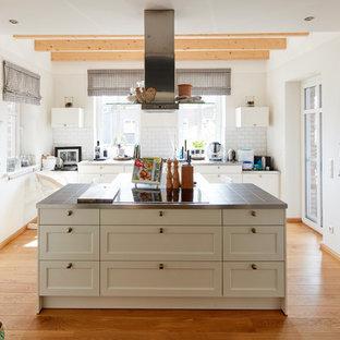 Cette photo montre une cuisine ouverte parallèle nature de taille moyenne avec un placard à porte shaker, des portes de placard blanches, un plan de travail en carrelage, une crédence blanche, une crédence en carrelage métro, un sol en bois brun, un îlot central, un sol marron et un plan de travail gris.