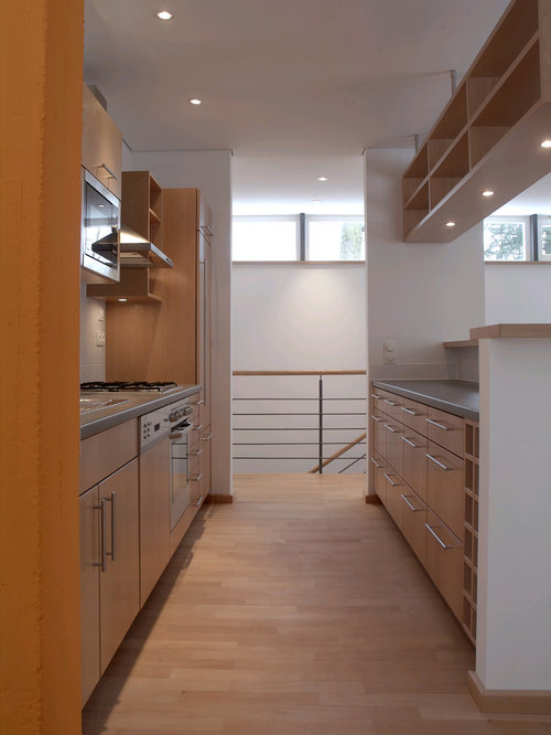 Zweizeilige mittelgroße offene moderne küche mit flächenbündigen schrankfronten hellbraunen holzschränken küchenrückwand in