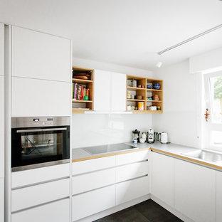 Kleine Nordische Küche ohne Insel in L-Form mit Waschbecken, flächenbündigen Schrankfronten, weißen Schränken, Küchenrückwand in Weiß, Glasrückwand, Küchengeräten aus Edelstahl und schwarzem Boden in Köln