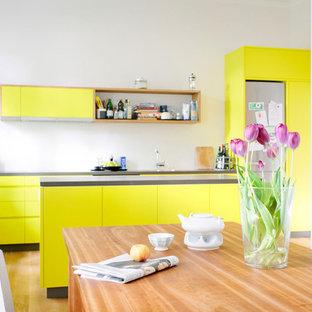 ケルンの中サイズの北欧スタイルのおしゃれなキッチン (フラットパネル扉のキャビネット、黄色いキャビネット、シルバーの調理設備の、無垢フローリング、茶色い床) の写真