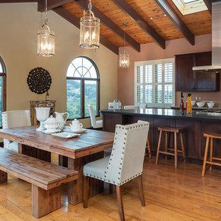 Diseño de cocina comedor de galera, rústica, grande, con suelo de madera pintada, armarios con paneles lisos, puertas de armario de madera en tonos medios, encimera de mármol, salpicadero rosa y una isla