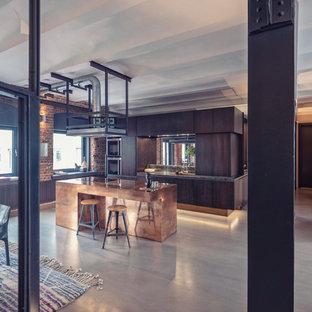 Offene, Zweizeilige, Große Industrial Küche mit flächenbündigen Schrankfronten, braunen Schränken, Rückwand aus Spiegelfliesen, Küchengeräten aus Edelstahl, Betonboden, Kücheninsel, grauem Boden und brauner Arbeitsplatte in Nürnberg