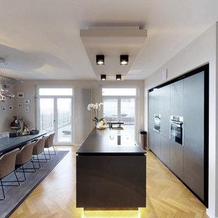 Zweizeilige, Große Moderne Wohnküche mit flächenbündigen Schrankfronten, schwarzen Schränken, schwarzen Elektrogeräten, braunem Holzboden, schwarzer Arbeitsplatte, Unterbauwaschbecken, Kücheninsel und beigem Boden in Nürnberg