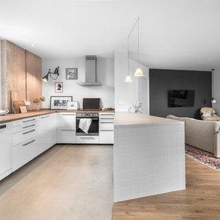 ハンブルクの巨大なエクレクティックスタイルのおしゃれなキッチン (シングルシンク、フラットパネル扉のキャビネット、白いキャビネット、木材カウンター、ピンクのキッチンパネル、石スラブのキッチンパネル、コンクリートの床、グレーの床) の写真