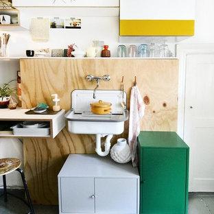 Kleine Eklektische Küche mit Landhausspüle, Rückwand aus Holz, gebeiztem Holzboden und grauem Boden in Berlin