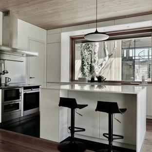 Moderne Küche in L-Form mit flächenbündigen Schrankfronten, weißen Schränken, Küchengeräten aus Edelstahl, braunem Holzboden, Kücheninsel, braunem Boden, weißer Arbeitsplatte und Holzdecke in Berlin