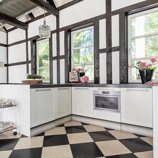 Geschlossene, Mittelgroße Landhaus Küche in U-Form mit flächenbündigen Schrankfronten, weißen Schränken, Küchengeräten aus Edelstahl, Halbinsel und grauer Arbeitsplatte in Sonstige