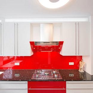 Offene, Mittelgroße Moderne Küche ohne Insel in U-Form mit Einbauwaschbecken, flächenbündigen Schrankfronten, weißen Schränken, Granit-Arbeitsplatte, Küchenrückwand in Rot, Rückwand aus Glasfliesen, schwarzen Elektrogeräten und Porzellan-Bodenfliesen in Stuttgart