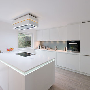 Photo of a large contemporary galley eat-in kitchen in Stuttgart with an integrated sink, flat-panel cabinets, white cabinets, solid surface benchtops, blue splashback, glass sheet splashback, light hardwood floors, with island and stainless steel appliances.