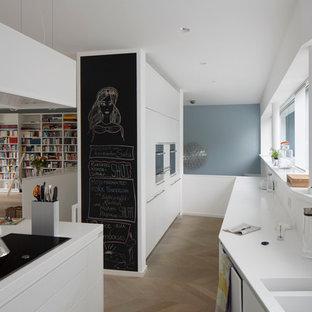 Offene, Große Moderne Küche mit integriertem Waschbecken, flächenbündigen Schrankfronten, weißen Schränken, Mineralwerkstoff-Arbeitsplatte, Küchenrückwand in Weiß, hellem Holzboden und Kücheninsel in Köln