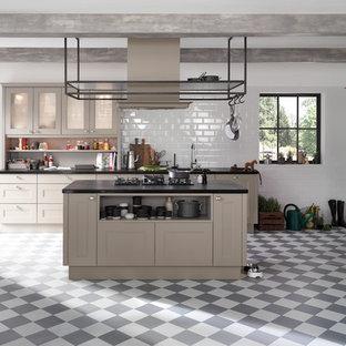 Inredning av ett klassiskt kök med öppen planlösning, med en nedsänkt diskho, luckor med infälld panel, grå skåp, vitt stänkskydd, stänkskydd i tunnelbanekakel, svarta vitvaror, en köksö, cementgolv och flerfärgat golv