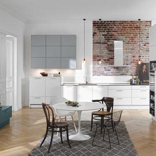 Große Moderne Wohnküche mit hellem Holzboden in Hannover