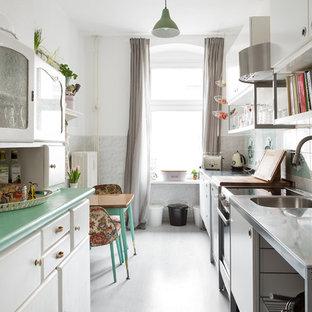 ベルリンの小さいシャビーシック調のおしゃれなキッチン (ドロップインシンク、フラットパネル扉のキャビネット、白いキャビネット、ステンレスカウンター、マルチカラーのキッチンパネル、セラミックタイルのキッチンパネル、リノリウムの床、アイランドなし) の写真