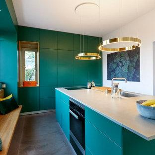 Geschlossene, Große Moderne Küche in L-Form mit Unterbauwaschbecken, flächenbündigen Schrankfronten, grünen Schränken, Elektrogeräten mit Frontblende, Porzellan-Bodenfliesen, Kücheninsel, grauem Boden und grauer Arbeitsplatte in Hannover