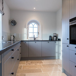 Inspiration for a mid-sized country l-shaped open plan kitchen in Other with a drop-in sink, louvered cabinets, blue cabinets, white splashback, glass sheet splashback, black appliances, slate floors, no island, beige floor and black benchtop.
