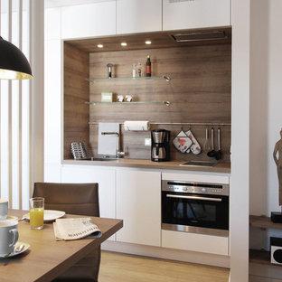 他の地域の中くらいの北欧スタイルのおしゃれなキッチン (フラットパネル扉のキャビネット、白いキャビネット、シングルシンク、木材カウンター、茶色いキッチンパネル、木材のキッチンパネル、シルバーの調理設備、クッションフロア、茶色い床、茶色いキッチンカウンター) の写真