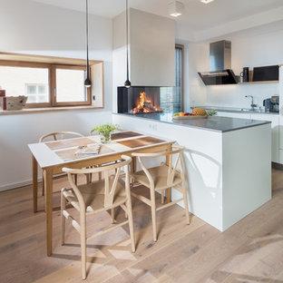 Einzeilige, Kleine Skandinavische Wohnküche mit braunem Holzboden, Einbauwaschbecken, flächenbündigen Schrankfronten, weißen Schränken, Küchenrückwand in Weiß und Kücheninsel in Hamburg