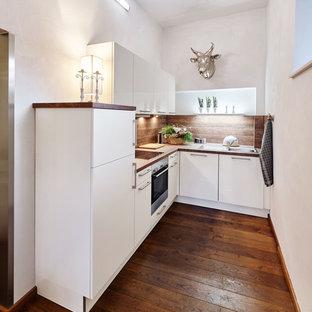 デュッセルドルフの小さいコンテンポラリースタイルのおしゃれなキッチン (フラットパネル扉のキャビネット、白いキャビネット、茶色いキッチンパネル、パネルと同色の調理設備、無垢フローリング、アイランドなし、木材カウンター、ドロップインシンク) の写真