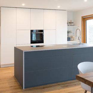 Новые идеи обустройства дома: большая линейная кухня-гостиная в стиле модернизм с плоскими фасадами, белыми фасадами, столешницей из ламината, островом, синей столешницей, монолитной раковиной, паркетным полом среднего тона и коричневым полом