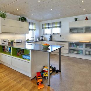 Mittelgroße, Offene Moderne Küche in U-Form mit flächenbündigen Schrankfronten, weißen Schränken, Küchenrückwand in Weiß, Elektrogeräten mit Frontblende, Halbinsel, grauem Boden, grauer Arbeitsplatte und Glasrückwand in München