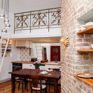 ベルリンの小さいシャビーシック調のおしゃれなキッチン (濃色無垢フローリング、ドロップインシンク、フラットパネル扉のキャビネット、白いキャビネット、木材カウンター、ミラータイルのキッチンパネル、アイランドなし) の写真