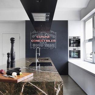 Ispirazione per una grande cucina minimal con lavello sottopiano, ante bianche, isola, top in marmo, elettrodomestici in acciaio inossidabile, ante lisce e pavimento in cemento