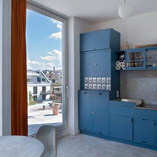 Einzeilige, Kleine Moderne Wohnküche ohne Insel mit Doppelwaschbecken, blauen Schränken, Küchenrückwand in Grau, Betonboden, flächenbündigen Schrankfronten, Rückwand aus Steinfliesen und Elektrogeräten mit Frontblende in Frankfurt am Main