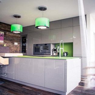 Foto de cocina contemporánea, abierta, con puertas de armario blancas, encimera de vidrio y una isla