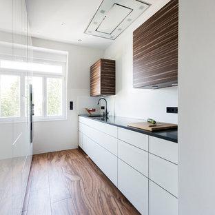 Zweizeilige, Geschlossene, Kleine Moderne Küche ohne Insel mit flächenbündigen Schrankfronten, weißen Schränken, Küchenrückwand in Weiß, dunklem Holzboden, braunem Boden, schwarzer Arbeitsplatte und integriertem Waschbecken in Frankfurt am Main