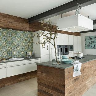 フランクフルトの大きいコンテンポラリースタイルのおしゃれなアイランドキッチン (フラットパネル扉のキャビネット、白いキャビネット、マルチカラーのキッチンパネル、シルバーの調理設備の、ドロップインシンク、御影石カウンター、セラミックタイルのキッチンパネル、コンクリートの床) の写真