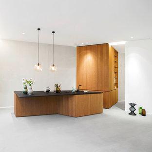 Mittelgroße Moderne Küche mit flächenbündigen Schrankfronten, hellbraunen Holzschränken, Betonboden, Kücheninsel und grauem Boden in Berlin