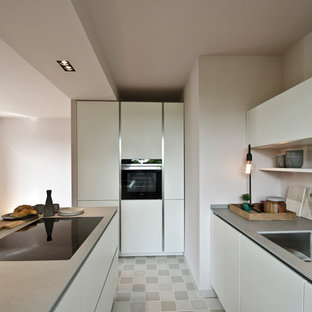 ハノーファーの小さいモダンスタイルのおしゃれなキッチン (白いキャビネット、タイルカウンター、ピンクのキッチンパネル、セメントタイルの床、アンダーカウンターシンク) の写真