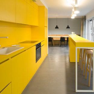 ミュンヘンの小さいコンテンポラリースタイルのおしゃれなキッチン (ドロップインシンク、フラットパネル扉のキャビネット、黄色いキャビネット、黄色いキッチンパネル、黒い調理設備、クッションフロア、グレーの床) の写真