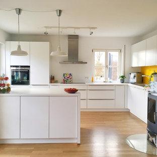 ミュンヘンの広いコンテンポラリースタイルのおしゃれなキッチン (一体型シンク、フラットパネル扉のキャビネット、白いキャビネット、黄色いキッチンパネル、シルバーの調理設備、無垢フローリング、白いキッチンカウンター) の写真