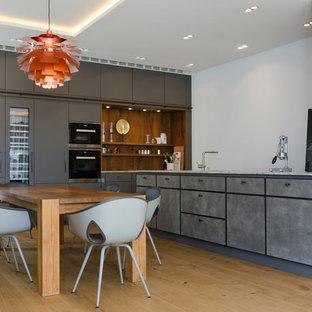 Große Moderne Wohnküche ohne Insel in L-Form mit flächenbündigen Schrankfronten, schwarzen Elektrogeräten, braunem Holzboden, grauen Schränken, Marmor-Arbeitsplatte und braunem Boden in Hamburg