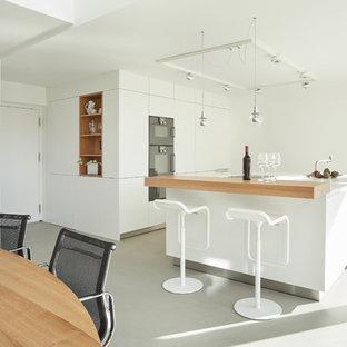 Einzeilige, Mittelgroße Moderne Wohnküche mit flächenbündigen Schrankfronten, weißen Schränken, schwarzen Elektrogeräten, Vinylboden, Kücheninsel, grauem Boden und weißer Arbeitsplatte in Stuttgart