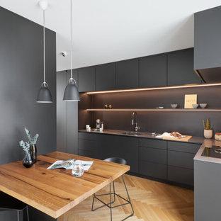 Offene Moderne Küche in L-Form mit integriertem Waschbecken, flächenbündigen Schrankfronten, schwarzen Schränken, Edelstahl-Arbeitsplatte, Küchenrückwand in Schwarz und hellem Holzboden in München