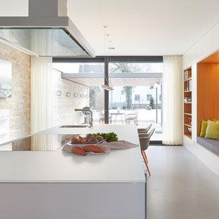 シュトゥットガルトの広いコンテンポラリースタイルのおしゃれなキッチン (一体型シンク、フラットパネル扉のキャビネット、白いキャビネット、ガラスカウンター、ベージュキッチンパネル、石スラブのキッチンパネル、クッションフロア、グレーの床、白いキッチンカウンター) の写真