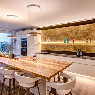 Zweizeilige, Mittelgroße Moderne Küche mit integriertem Waschbecken, flächenbündigen Schrankfronten, weißen Schränken, Küchenrückwand in Gelb, schwarzen Elektrogeräten, braunem Holzboden, Kücheninsel, braunem Boden und grauer Arbeitsplatte in Sonstige