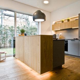 Zweizeilige Moderne Wohnküche mit flächenbündigen Schrankfronten, hellen Holzschränken, Küchenrückwand in Grau, schwarzen Elektrogeräten, braunem Holzboden, Halbinsel, braunem Boden und schwarzer Arbeitsplatte in Nürnberg