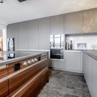 Offene, Große Moderne Küche mit flächenbündigen Schrankfronten, grauen Schränken, Küchenrückwand in Weiß, Rückwand aus Metrofliesen, schwarzen Elektrogeräten und Kücheninsel in München