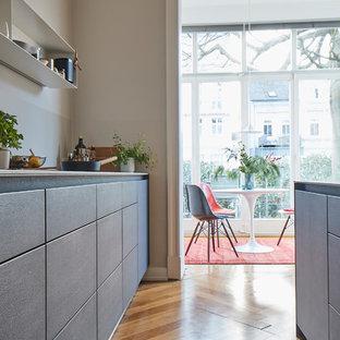 ハンブルクの大きいモダンスタイルのおしゃれなキッチン (ドロップインシンク、フラットパネル扉のキャビネット、グレーのキャビネット、木材カウンター、グレーのキッチンパネル、塗装フローリング、茶色い床、グレーのキッチンカウンター) の写真