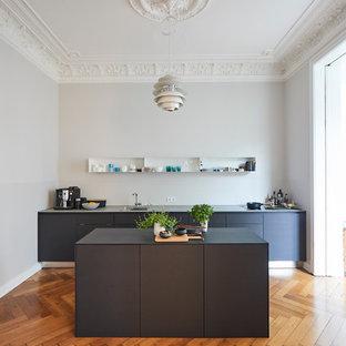 ハンブルクの広いトランジショナルスタイルのおしゃれなキッチン (ドロップインシンク、フラットパネル扉のキャビネット、グレーのキャビネット、木材カウンター、グレーのキッチンパネル、塗装フローリング、茶色い床、グレーのキッチンカウンター) の写真