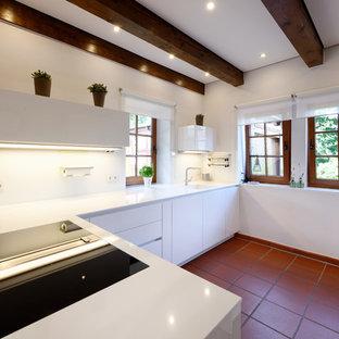 エッセンの中サイズのカントリー風おしゃれなキッチン (一体型シンク、フラットパネル扉のキャビネット、白いキャビネット、白いキッチンパネル、ガラス板のキッチンパネル、黒い調理設備、テラコッタタイルの床、赤い床、白いキッチンカウンター) の写真