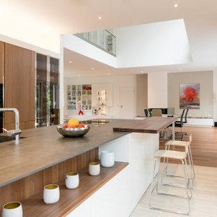 Offene, Zweizeilige, Große Moderne Küche mit Unterbauwaschbecken, flächenbündigen Schrankfronten, hellbraunen Holzschränken, Kücheninsel, beigem Boden und grauer Arbeitsplatte in Düsseldorf