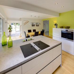 フランクフルトの大きいコンテンポラリースタイルのおしゃれなキッチン (ドロップインシンク、フラットパネル扉のキャビネット、白いキャビネット、コンクリートカウンター、緑のキッチンパネル、シルバーの調理設備、無垢フローリング、茶色い床、グレーのキッチンカウンター) の写真